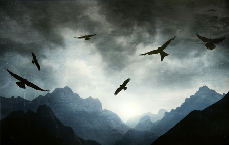 Beautiful gothic image of a mountain range with several hawks flying towards a dramatic sky in backlight 免版税图像