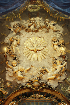 Architectural detail of a chapel with many cherubs surrounding the dove of the Holy Spirit Stock Photo