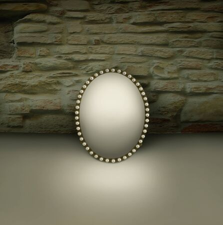 Small mirror with vintage frame decorated in pearls on a brick wall background Reklamní fotografie