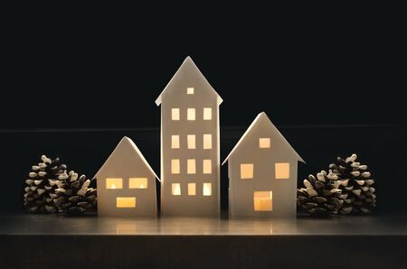 Beautiful winter landscape with small houses made of paper illuminated inside and with pine cones
