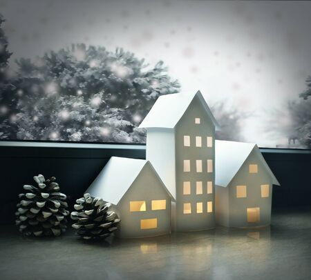 Beautiful winter landscape with small houses made of paper illuminated inside and with pine cones and window with some trees and snow 免版税图像