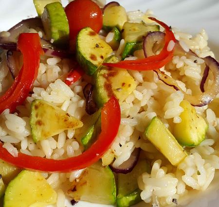comidas saludables: risotto vegetal hecha de calabacín, pimentón, tomates cherry y cebolla roja en la placa blanca