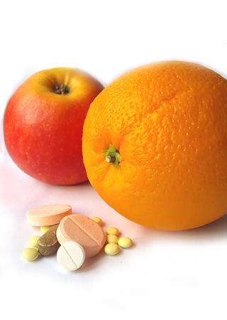 c vitamin: Orange and apple fruit or tablets on white background