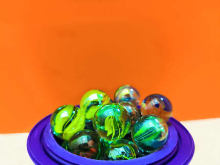 Many Green Round Marbles Arranged In Blue Pot
