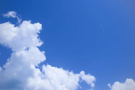 spaciousness: Blue sky, white clouds and trace of plane above them Stock Photo