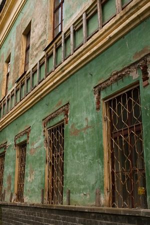 Old green shabby wall of an abandoned building with barred windows and stairs