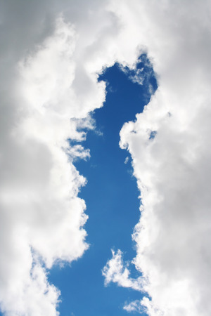 discontinuity: Vertical cleft between the white-grey clouds, through which peeps the blue sky Stock Photo