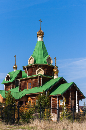 Wooden church with green roofs and gold domes on the blue sky background. The snapshot  was made in the Urals village of Kashino the Sverdlovsk region in Russia.