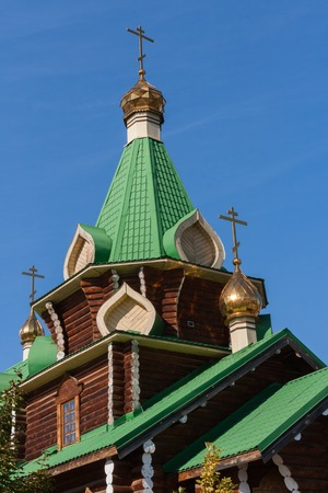 made russia: Close-up of green roofs and domes of wooden church on the blue sky background. The snapshot  was made in the Urals village of Kashino the Sverdlovsk region in Russia.