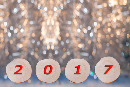 annual ring annual ring: Four alder  saw cuts  and red date 2017 on Christmas golden bokeh background. New year or Christmas background. Stock Photo