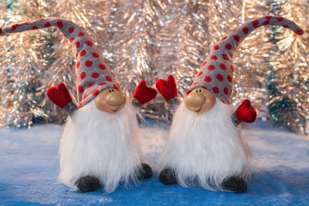 facing each other: Two cheerful gnome with your hands facing each other on a silver background. Christmas or New Year picture. Stock Photo