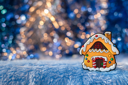 Small decorative house, simulating gingerbread on a beautiful Golden-blue bokeh background. Christmas and New Year background.