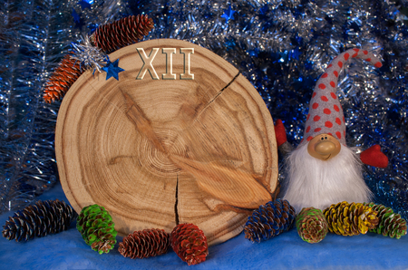 Larch saw cut in the form of dial with arrows, painted fir cones and gnome on blue tinsel background. Christmas and New Year background.