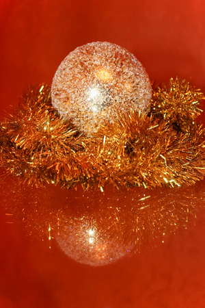 crystalline gold: Christmas composition. Beautiful golden sparkling sphere and shiny tinsel are reflect in the glass surface.