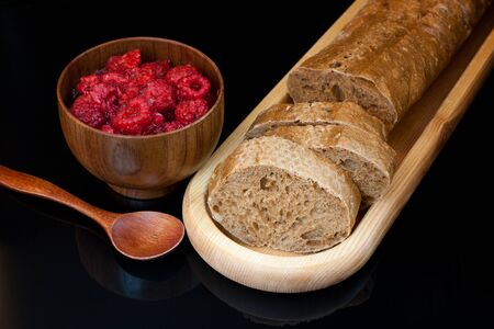 crackling: Top view to wooden plate with fresh sliced bread, cup with raspberries and spoon on black background. Stock Photo