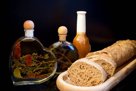 recent: Composition on dark background. Wooden plate with fresh sliced bread and small glass bottles with oil and spices. Stock Photo