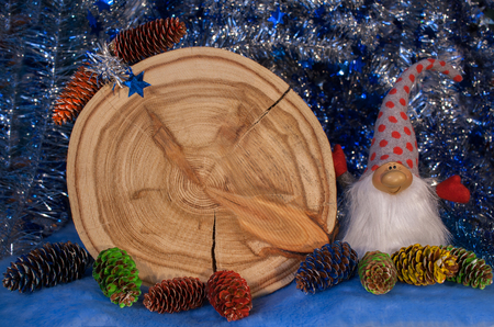 annual ring annual ring: Larch saw cut in the form of dial with arrows, painted fir cones and gnome on blue tinsel background. Christmas and New Year background.