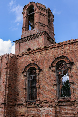 cultic: A ruined church. Part of brick wall and bell tower on blue sky background. The photo was taken in Russia in Ugolnoye village in August 2015. Stock Photo