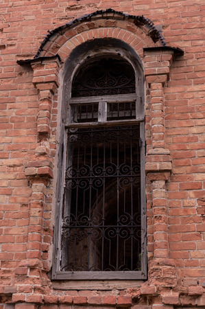 window opening: Close-up of window opening and lattice on destroyed  brick wall. The photo was taken in Russia in Ugolnoye village in August 2015.