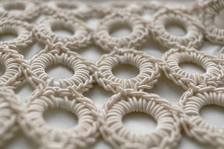 intertwined: Close-up of braided cord pattern rings on white textured background. Selective focus.