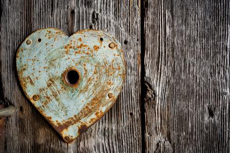 door lock love: Rusty old trim on keyhole in shape of heart on old wooden door. Stock Photo