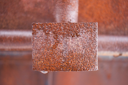 oxidate: Wet rusty metal rectangular plate in middle of frame. Background blurred. Stock Photo