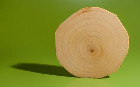 Uno de aliso pulido y aceitado corte de sierra se coloca en el fondo verde.