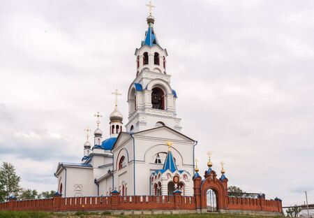 Orthodox temple. Church of the Dormition at cloudy summer day. Novoutkinsk, Russia. Stock Photo