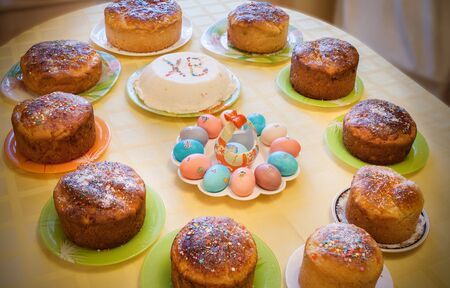 Easter cuisine. Easter cakes, curd Easter and dyed eggs stand on covered yellow tablecloth table. Stock Photo