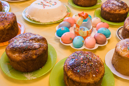 Easter cuisine. Easter cakes, curd Easter and dyed eggs stand on covered yellow tablecloth table. Side view.