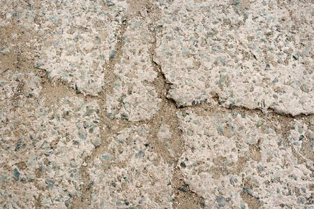 Stone background. Close-up part of pavement made of concrete with small pebbles and sand, hammered into cracks.