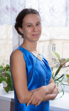 Beautiful young 20s girl in blue dress is standing near window and looking at camera.