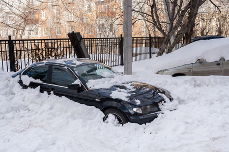 climatic: Cars stucked in deep snow in the courtyard of house in winter. Stock Photo