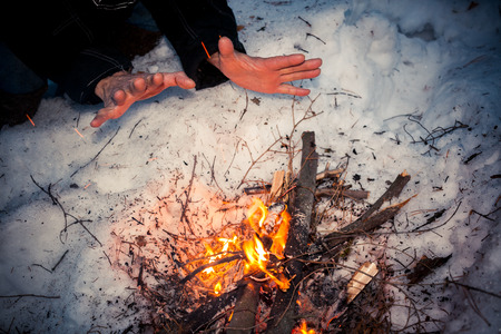Frozen male hands are warming over flames of bonfire at winter night.