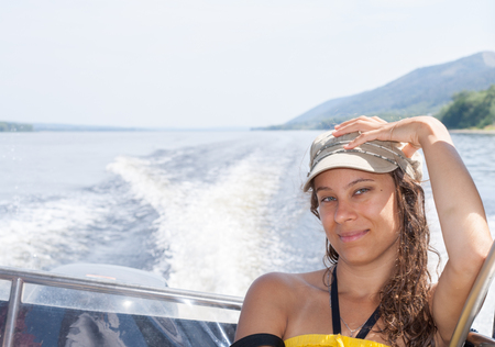 Young girl is riding on motorboat on the river in a hot summer afternoon.
