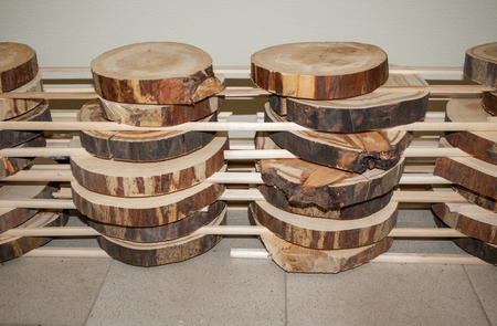 Folded stack of transverse wooden saw cuts stands vertically on floor.