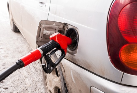 Filling hose with gasoline is inserting in fuel hole gray car.