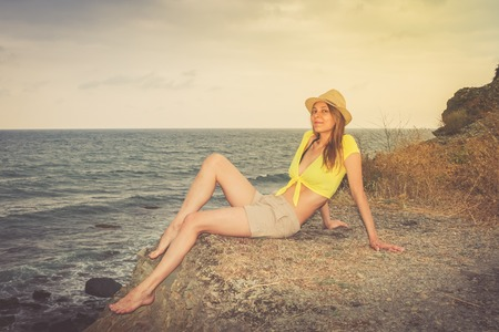 Young girl in the hat, shorts and a short shirt is sitting on a wild stony sea coast.