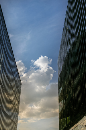 The clearance between two large modern buildings, and is seen the blue sky with clouds in it. Banco de Imagens
