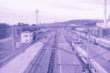 Surrealistic violet toned perspective image of the large railway station with railway tracks and trains. Top view. Stock Photo