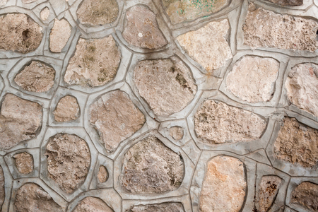 Background of natural porous stones of arbitrary shape, fastened together with a cement screed.