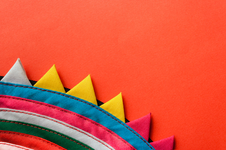 Close-up round colorful handmade striped stitched fabric with triangular edge on red background. Stock Photo