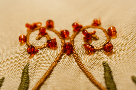 Close-up embroidered with satin stitch curls, with sewn red beads.