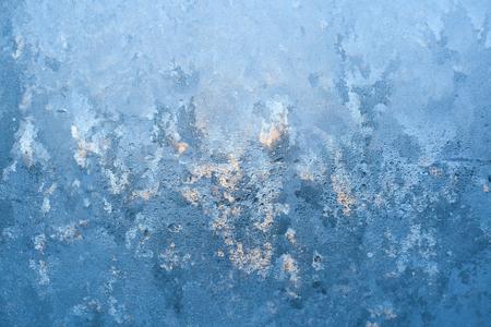 Textured frosty pattern on window lit by winter sun.
