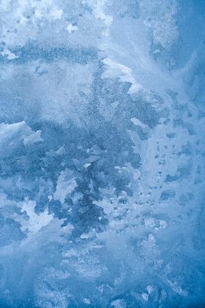 Blue frozen glass pane with winter florid pattern.