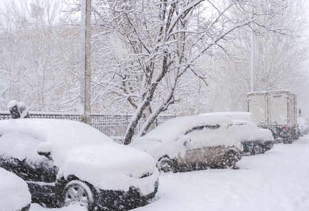 Parked snow-covered cars during plentiful snowfall in winter day.