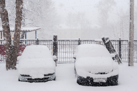 Two parked snow-covered cars in courtyard during plentiful snowfall.