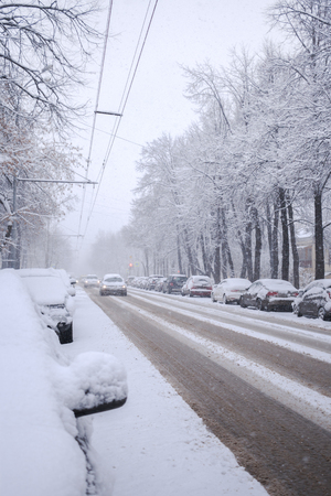 Snow-covered city road with driving cars and snow-covered cars on roadside during snowfall.