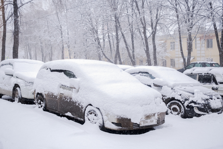 Snow-covered parked cars standing in snowdrift during snowfall.