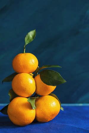 Hight pile of yellow mandarins with leaves is lying on blue background. Stock fotó